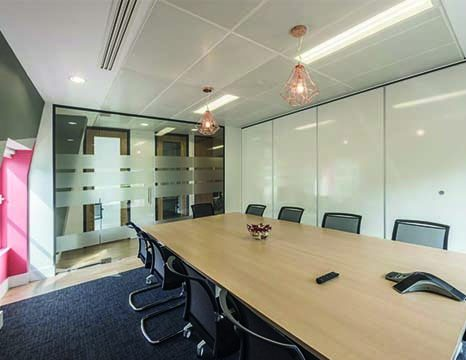A boardroom with wooden table next to a glass partition window