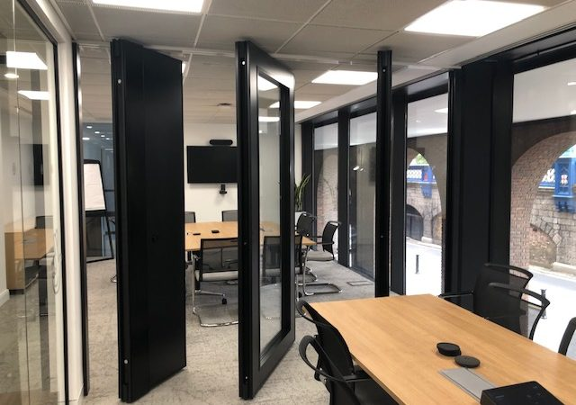 Black folding sliding doors in an office
